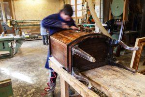Carpenter restoring Wooden Furniture in his workshop